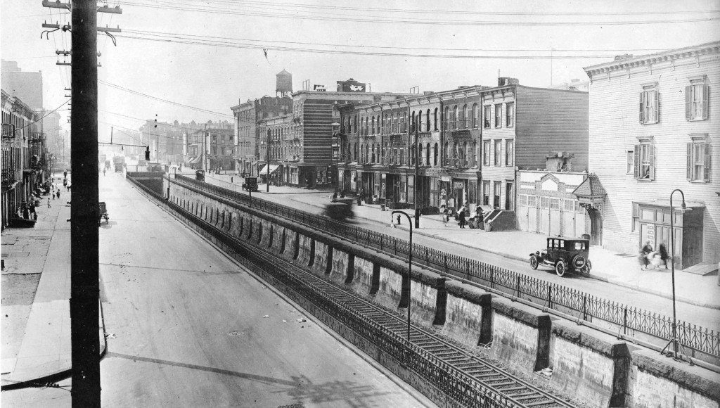 Atlantic Ave looking west from the Sackman St bridge. Long Island Railroad emerging from a tunnel. New 1920s cars zoom along as kids play on the sidewalk. Brooklyn, New York. 1922