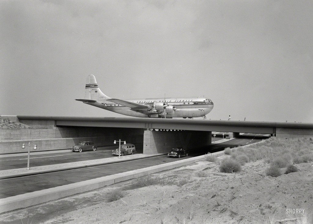 "August 25, 1949. ""New York International Airport, Idlewild. Bridge with plane."" A Boeing 377 Stratocruiser, the Pan Am Clipper Seven Seas. Large-format acetate negative by Gottscho-Schleisner."