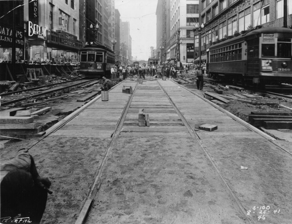 Multiple streetcars are in view on this busy scene in 1941 from during construction of the State Street Subway (used by CTA Red Line service, today). Like today, many surface transit lines share State Street. Since streetcars can't just divert themselves around an obstruction, temporary tracks had to be built to reroute the car lines around excavation sites for the many entrances to the subway (and subsurface mezzanines).   Based on signs visible in these pictures, services these streetcars were providing were predecessor services to routes that use State Street today, including the #29 State, #36 Broadway and #62 Archer.